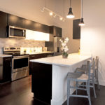 Black Kitchen Cabinets and Bar with Stools